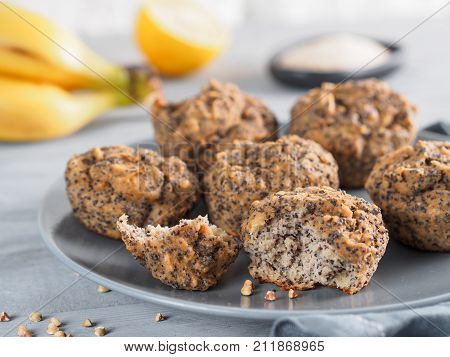 Close-up view of healthy gluten-free homemmade banana muffins with buckwheat flour. Vegan muffins with poppy seeds on gray plate over gray wooden table