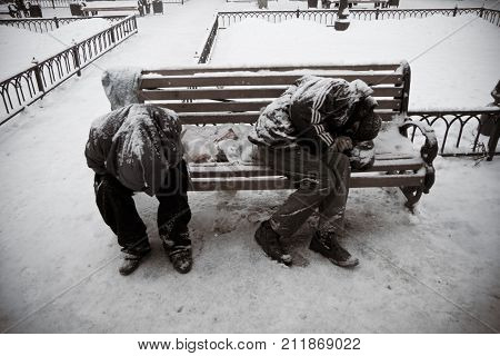 Voronezh, Russia - December 21, 2012: Unknown homeless or alcoholics or drug addicts are sleeping on the bench in winter park.