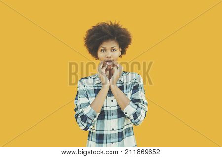 Young female teenager in plaid shirt making surprised emotional face in front of yellow wall; Brazilian girl in checkered shirt feeling joyous surprise with her hands on face isolated color