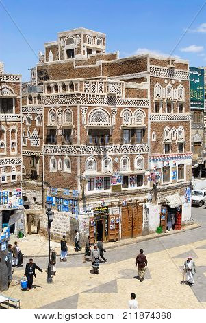 SANAA, YEMEN - SEPTEMBER 09, 2006: Unidentified people walk by the street of the city in Sanaa, Yemen. The old city of Sanaa is a UNESCO World heritage site.