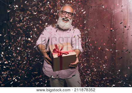 Modern senior bearded man gives a gift and happy smile in gold confetti. Happy New Year 2018. Merry Christmas to you!