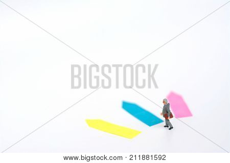Three direction arrow choices left right or move forward miniature model figure of businessman are taking decisions for the future, choice way in business concept.