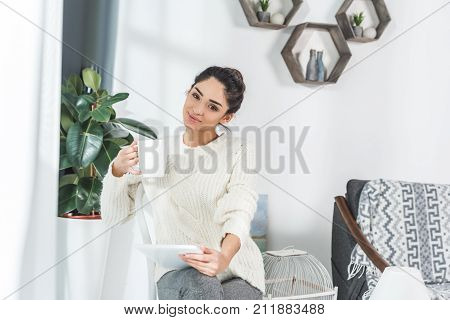 smiling brunette girl holding cup and digital tablet at home poster