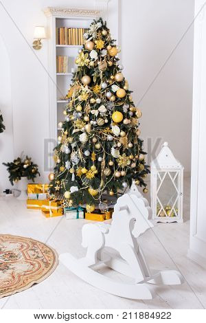 Wooden toy horse giftboxes golden christmas decorations balls hanging on a decorative christmas tree. concept New Year celebration background.