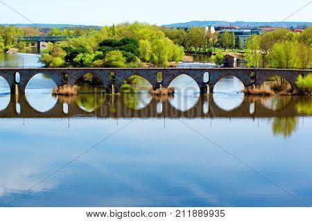 Bridge Puente de Piedra across River Douro with Water Reflection in Sunny Day on Cityscape background. Zamora Castilla and Leon Spain