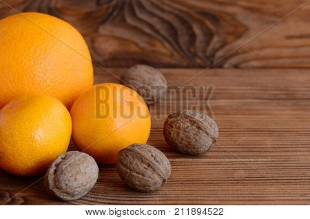 Mandarin, orange, walnuts on a wooden table. Natural sources of vitamins and minerals. Healthy eating. Brown wooden background with copy space for text