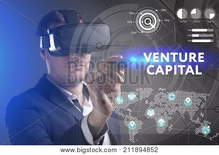 Business Technology Internet and network concept. Young businessman working in virtual reality glasses sees the inscription: Venture capital
