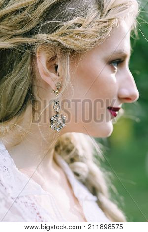 Vintage earring on the bride's ear. Close-up portrait of the bride. Artwork. Selective focus on an ear