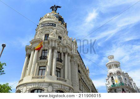 MADRID - JUN. 6, 2013: Metropolis Building (Edificio Metropolis) and Grassy Building (Edificio Grassy) in Madrid, Spain. Metropolis Building is one of the most famous Beaux-Arts style landmark.