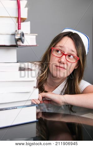 Young Nurse With Cap Looking At Stack Of Books