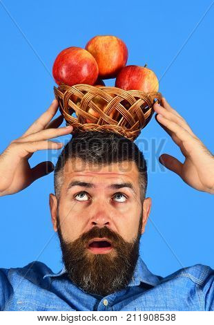 Farmer With Concentrated Face Holds Red Apples On Head.
