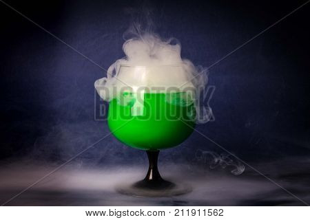 Abstract art. Hookah smoke into cocktail glass on a black background. Witch potion background for Halloween. Unusual bar drink. Drink in the glass with the effect of dry ice.