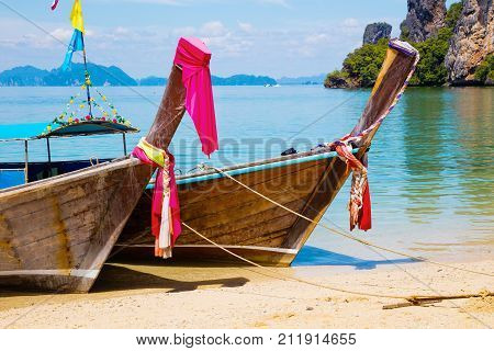 Traditional Thai longtail boats moored at Aonang beach on sunny day