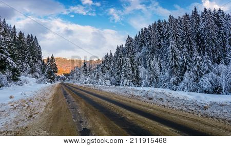 Snowy Road Through Mountains In Evening