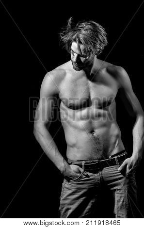 Handsome man or unshaven macho bodybuilder with stylish blond hair haircut showing sexy naked muscular torso with six packs and abs biceps triceps on black background
