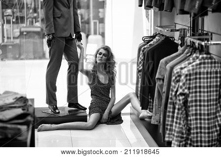 Pretty girl or beautiful woman with long curly hair wearing pink polka dot dress barefoot sits on floor at fashionable male mannequin in suit in shop and hanger racks with clothes for sale