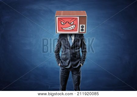 A self-assured businessman holds his hands in pockets and wears an old TV with an angry smiley face on his head. New personality. Be more aggressive. Proactivity at work.
