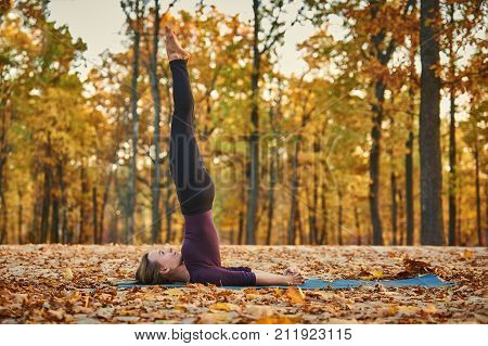 Beautiful young woman practices yoga asana Niralamba Sarvangasana - unsupported shoulderstand pose on the wooden deck in the autumn park