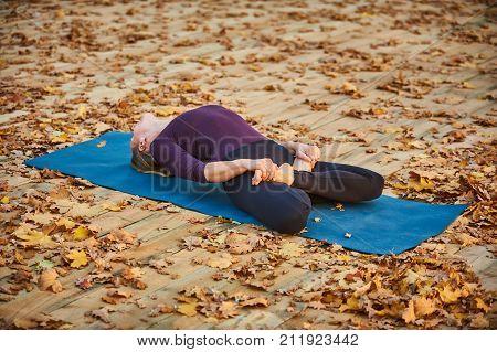 Beautiful young woman practices yoga asana Matsyasana - Fish pose on the wooden deck in the autumn park