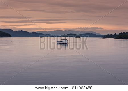 Boat in a lake at sunset in the Highlands of Scotland United Kingdom; Concept for travel in Scotland