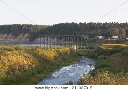 Remains of the Opokskogo hydroelectric complex in the rays of the setting sun. Village Threshold in Velikoustyugsky district, Vologda region, Russia