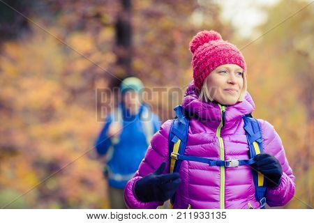 Happy couple hikers camping in beautiful yellow autumn forest and mountains. Young partnership teamwork man and woman walking with backpacks healthy lifestyle adventure camping on hiking trip.