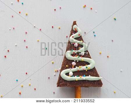Culinary background with Christmas tree shaped biscuits. Homemade sugar cakes glazed with royal icing. Copy space for your text. Top view.