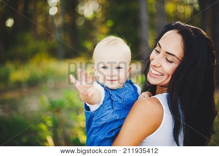 Young Beautiful Fashionable Mother With Long Brunette Hair Holding A Daughter's Blonde With Blue Eye