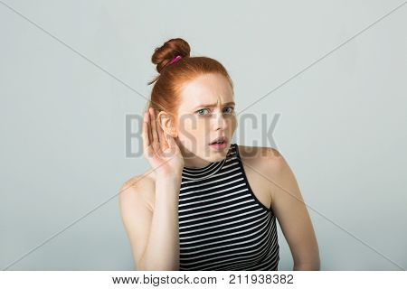 beautiful young girl with red hair on a light background curves and makes facial expressions