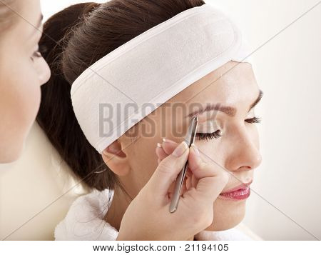 Tweezing eyebrow by beautician. Isolated. poster
