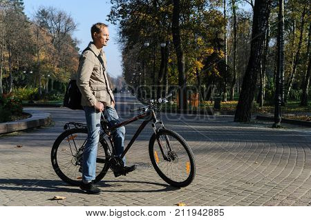 Man on a bicycle in the park. The cyclist stopped and is staring in the distance.