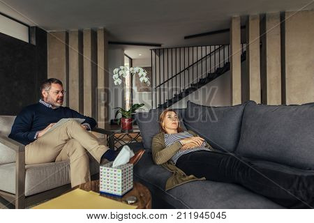 Depressed woman lying on sofa during psychotherapy session. Psychologist talking with female patient during therapy.