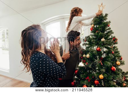 Family decorating a Christmas tree. Young man with his daughter on his shoulders helping her to place a star on Christmas tree.