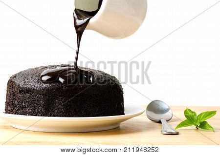 Hand pouring chocolate sauce on top of chocolate cake