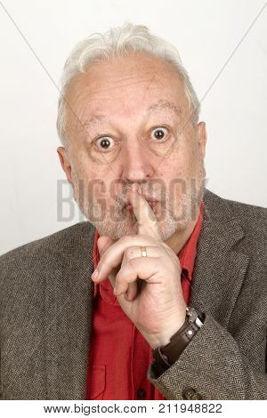 Senior laying trigger finger on mouth - on bright background