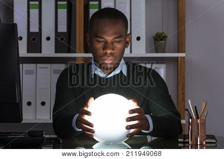 Portrait Of African Businessman Predicting Future With Crystal Ball On Desk At Office