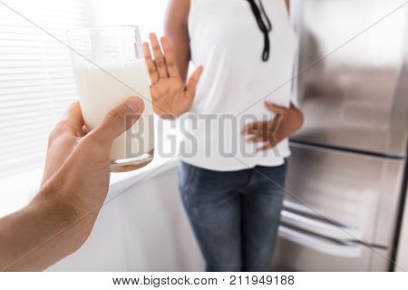Woman Rejecting Glass Of Milk Offered By Person