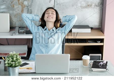 Asian office woman stretching body for relaxing while working with laptop computer at her desk office lifestyle business situation