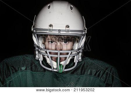 Low key harsh flash image of a boy in a football uniform