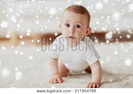 childhood, babyhood and people concept - happy little baby boy or girl crawling on floor at home over snow