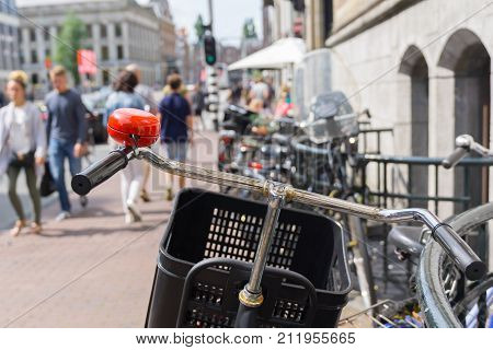 Focus on bicycle hanle bars and red bell in defocused blur background street scene with railing and unrecognizable people