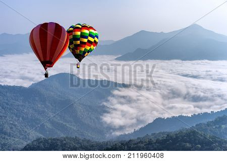 Hot air balloon with tourist is traveling into the peak of mountain and cloudscape at Doi Pha Tang in Chiangrai Provice Thailand. Beautiful hot air balloon and mist at sunrise. Traveler concept