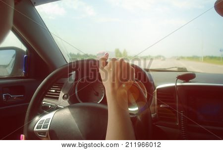 Car travel concept. The girl is driving the car on the road holding the steering wheel with one hand and listen to music from the car radio. Walkie talkie cb Radio transmitter on the car dashboard.