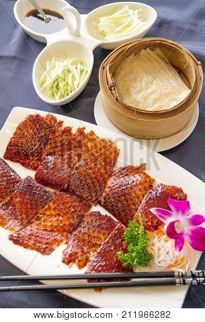 Peking duck or grilled duck skin served with fresh vegetable, sweet sauce and roasted wheaten Chinese pancakes
