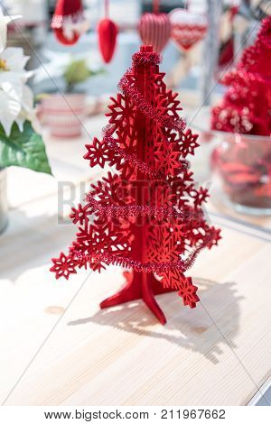 Red Christmas Tree Foam Model Decorated With Little Tinsel Garland Standing On Shelf And Shade Of Li