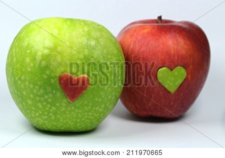 Red apple with green heart and green apple with red heart.