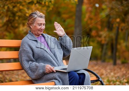An adult lovely woman in an autumn park sits on a bench and with whom she communicates on a laptop and waves them with her hand. Outside.