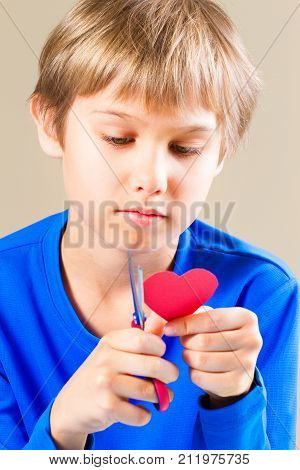 Child cutting red paper heart with scissors