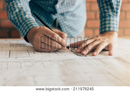 Close Up Hand Engineering Man Standing Examining Working On A Blueprint For New Project In Home Offi