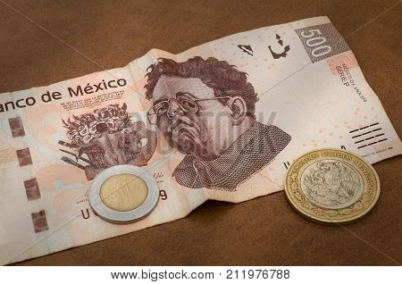 A 500 mexican pesos bill seems to be sad perhaps because of its weakness against the dollar. A coin of 1 peso and the back of one of 10 are also show.